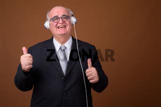 Overweight senior businessman listening music with headphones