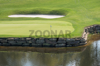 Challenging hole on luxury golf course with water and sand