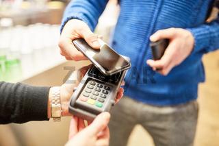 Kunde bezahlt kontaktlos mit Smartphone via NFC