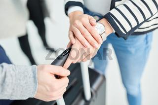 Passagier schaut ungeduldig auf seine Armbanduhr