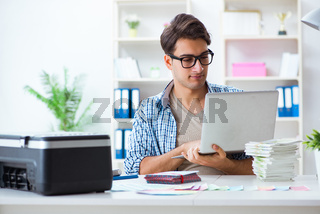 Young man employee working at copying machine in the office