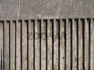 old exterior concrete wall with fluted vertical stripe design with a rough cast texture with shadow