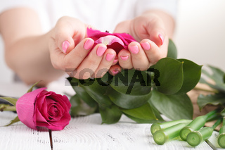 Hand of a florist woman full of rose petals for wedding
