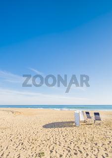 blauweiße stühle und windschutz an menschenleerem strand