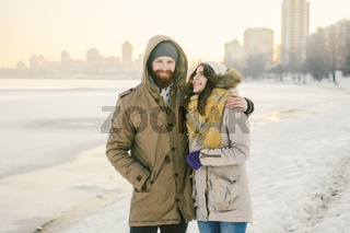 Theme love and date on nature. A young Caucasian heterosexual couple guy and girl walk in the winter along a frozen lake in winter. Bearded Man Hugging Woman. Valentine's day holiday