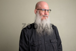 Mature bald man with long gray beard thinking and wearing eyeglasses