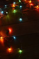 Christmas garland with lights on wooden background