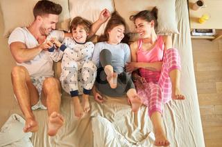 Familie mit zwei Kindern albert herum im Bett