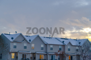 Snowy homes in Eagle Mountain against cloudy sky