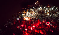 Dark background with tinsel and ball