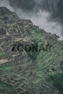 Vertical view of Machu Picchu lost city and mountains with clouds.