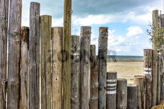 Palisade aus Holzstämmen am Sandstrand