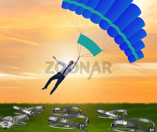 Businessman falling into trap on parachute