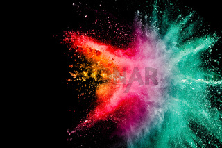 Abstract multicolored powder explosion on black background. Color dust particle splattered.
