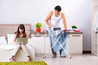 Man ironing, his lazy wife sitting