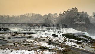 Rhine Falls in Switzerland on a winter evening with snow falling