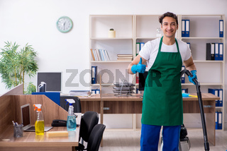 Young handsome contractor cleaning the office