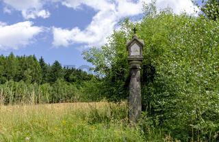 Grüne Landschaft mit alter steinerner Andachtssäule bei Harbach