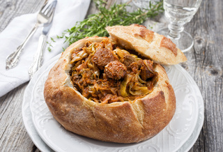 Traditional Polish kraut stew bigos with sausage and meat filled in white bread as closeup on a plate
