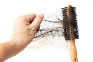 Hand grabbing lost hair on brush