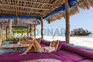 Relaxed woman in luxury tropical bar lounger, enjoying summer vacations on beautiful beach.
