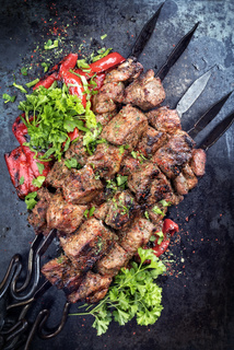 Traditional Russian shashlik on a barbecue skewer with paprika as closeup on an old board