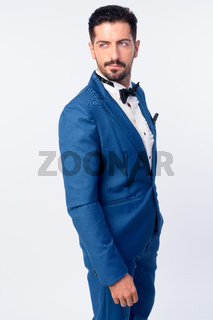 Portrait of young handsome bearded businessman in blue suit