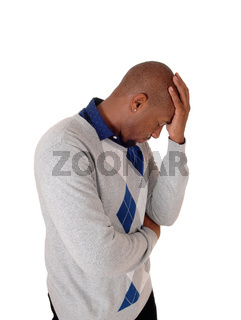 African man with his hand on his forehead, thinking