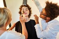 Hairstylist und Visagistin schminken Fotomodell