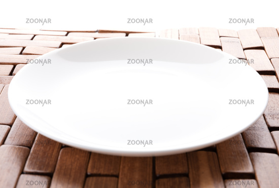 Isolated white plate on a wooden stand