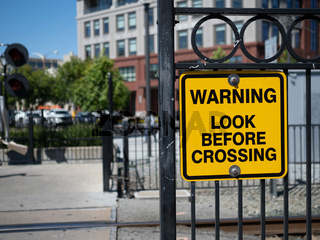 Warning look before crossing yellow warning sign at train crossing in city