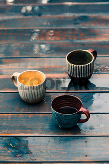 A couple of earthen cups with coffee and herbal tea on wooden wet table after rain