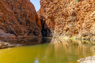 in the Australian outback there is a rugged rock formation with a waterhole
