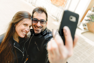Young couple in love making a selfie on the street posing as amateur models.