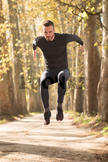 Sport running man in cross country trail run. Fit male runner exercise training and jumping outdoors in beautiful nature