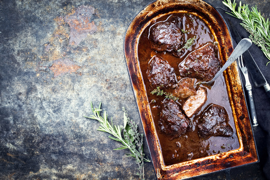 Traditional German braised veal cheeks in brown red wine sauce with mushroom and onions as top view in a stewpot with copy space left