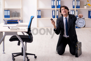 Young male employee in the office in time management concept