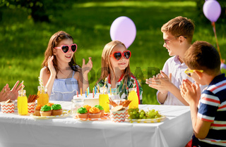happy kids with cake on birthday party in summer
