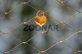 Goldenes herzförmiges Vorhängeschloss an einem Netz aus Stahlseilen