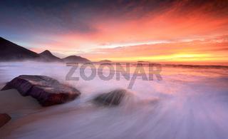 Ocean sunrise as large waves wash onto the beach