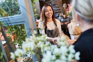 Floristin begrüßt Kunde mit Handschlag im Blumenladen