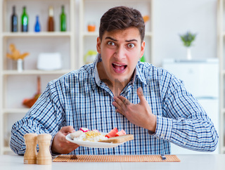 Young husband eating tasteless food at home for lunch
