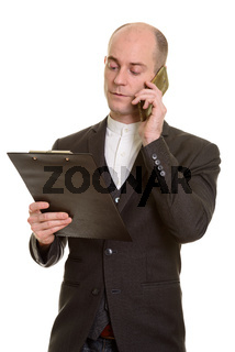Bald Caucasian businessman talking on mobile phone while reading
