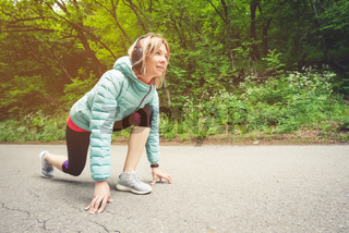 Athletic woman running in countryside road. Fitness female runner in ready start line pose outdoors in summer sprint challenge