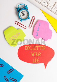 Word writing text De Clutter Your Life. Business concept for remove unnecessary items from untidy or overcrowded places Flat lay with copy space on bubble paper clock and paper clips.