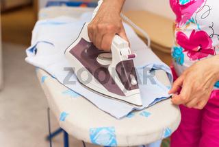 Senior woman close up ironing clothes