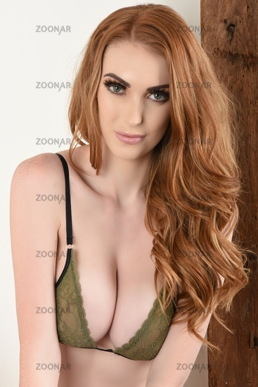 Sexy, busty Redhead dressed in green lacy Bra and Panties