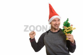 Happy Caucasian man holding Merry Christmas tree looking excited