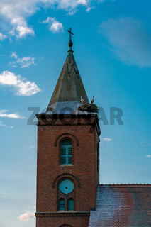 Church in Guelpe, Germany with storks breeding on the clock tower