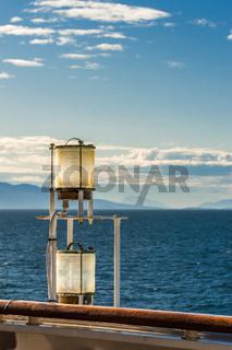Sunlit glass and metal sternlight of ship. Stephen's Passage, Alaska, USA.